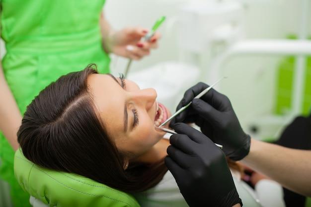 O homem do dentista está tratando os dentes ao cliente no consultório odontológico