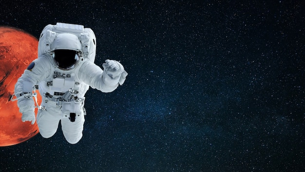 O homem do espaço em traje espacial voa no espaço estrelado com o planeta vermelho marte, copie o espaço para texto e design. papel de parede cosmos