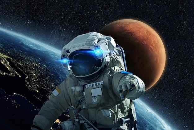 O homem do espaço em um traje espacial voa em um espaço aberto sobre um fundo do planeta azul terra e do planeta vermelho marte. o astronauta inicia uma missão no espaço sideral e viaja para marte. jornada no cosmos
