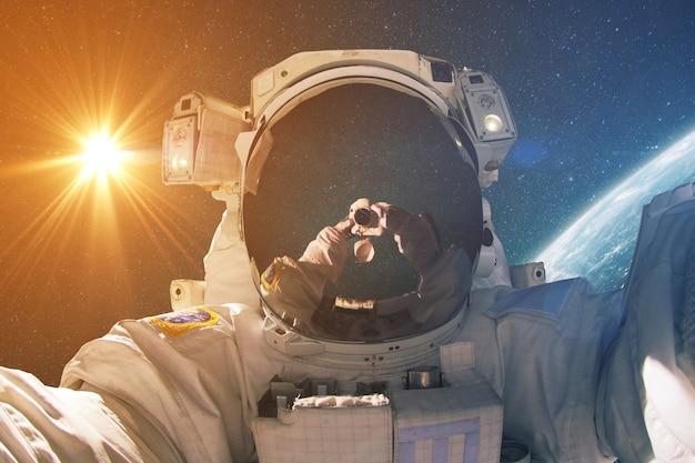 O homem do espaço faz selfie foto no espaço sideral com o sol e o planeta terra. o fotógrafo astronauta viaja e tira fotos no espaço profundo. conceito de viagens