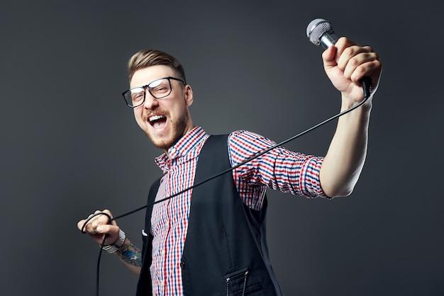 O homem do karaokê canta a música para o microfone, cantor com barba em fundo cinza. homem engraçado de óculos segurando um microfone na mão enquanto o cantor de karaokê canta a música