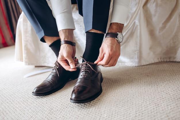 O homem do lado da cama colocando sapatos