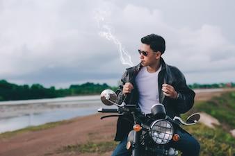 O homem do motociclista que senta-se fuma com seu velomotor ao lado do lago natural e bonito.