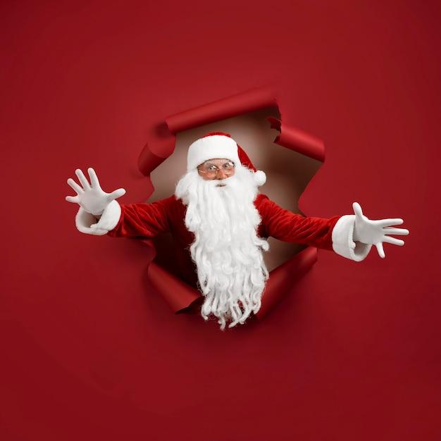 O homem do papai noel abriu os braços em diferentes direções e olhou emocionado através de um buraco de papel. homem barbudo com chapéu de papai noel, olhando pelo buraco no papel vermelho.