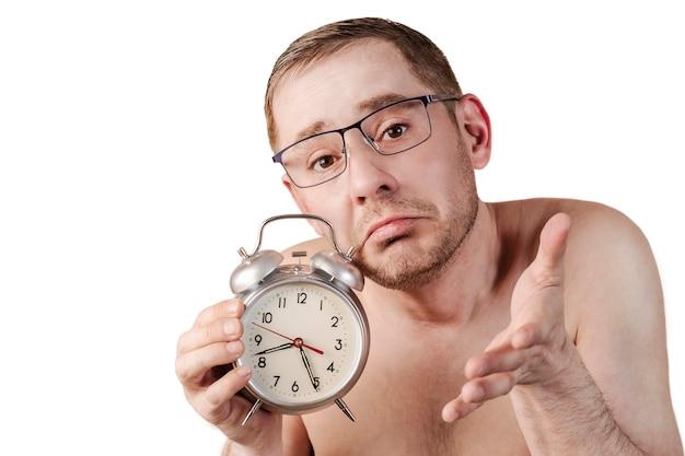 O homem dormia para trabalhar um homem com a mão levantada segura um despertador expressão facial engraçada