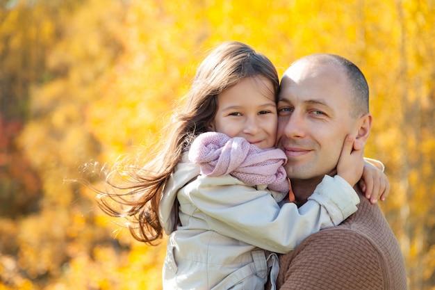 O homem dos óculos de sol abraça a filha bonita no fundo de árvores coloridas do outono