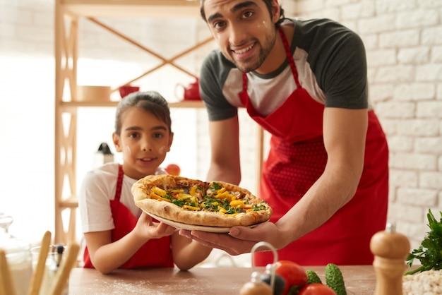 O homem e a menina cozinharam a pizza bonita na cozinha.