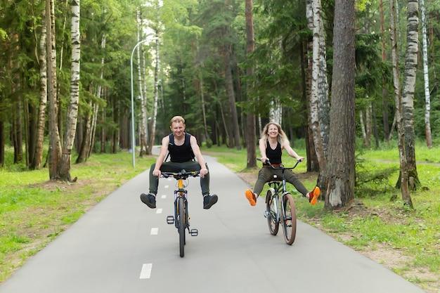 O homem e a mulher andam de bicicleta pela floresta