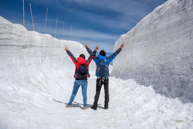O homem e a mulher espalharam a mão na passagem da neve na rota alpina de tateyama kurobe.