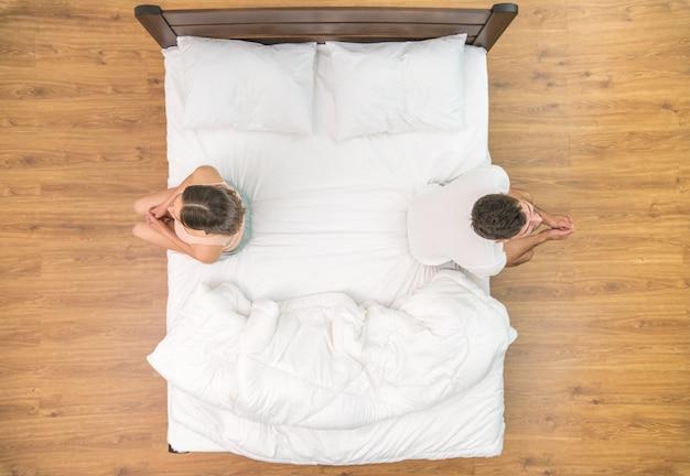 O homem e a mulher estão sentados na cama. vista de cima