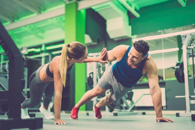 O homem e a mulher fazendo exercícios de flexão e gestos na academia