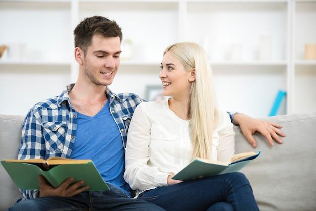 O homem e a mulher lendo livros no sofá