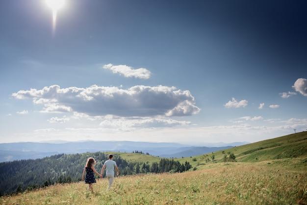 O homem e a mulher mantêm suas mãos juntas andando na colina em algum lugar nas montanhas