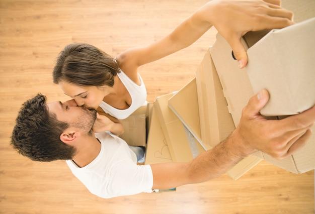 O homem e a mulher seguram caixas e se beijam. vista de cima