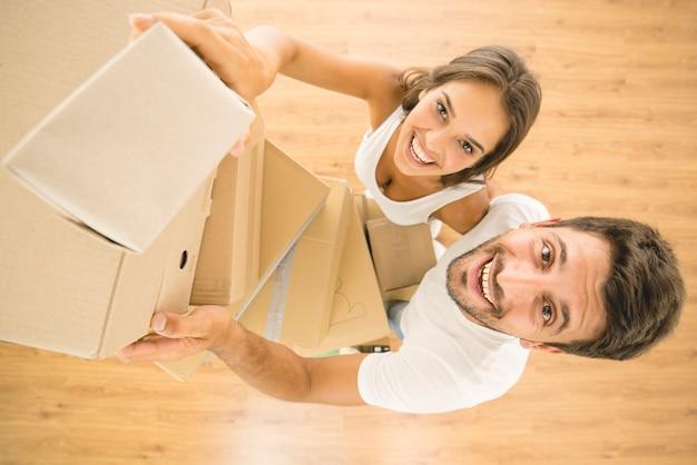 O homem e a mulher seguram uma caixa e olham para a câmera. vista de cima