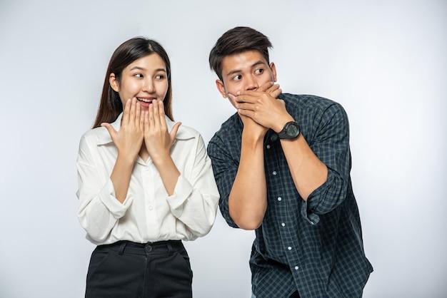 O homem e a mulher usavam camisas e cobriram a boca com as mãos em estado de choque