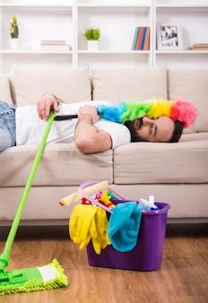 O homem é cansado e dormindo no sofá durante a limpeza em casa.