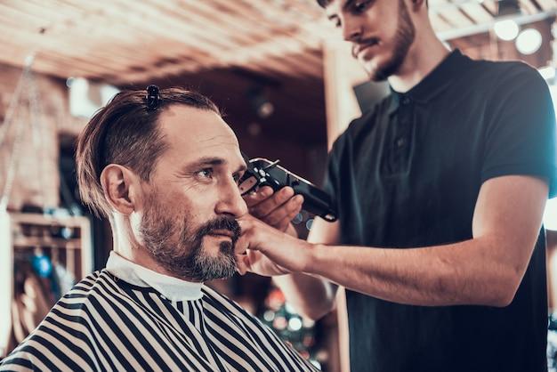 O homem é cortado na barbearia por um mestre profissional.