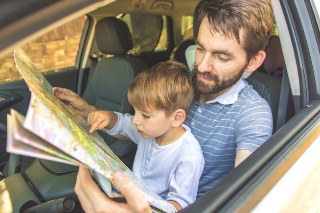 O homem e o filho olham para o mapa dentro do carro