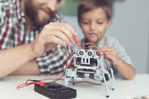 O homem e o menininho medem o desempenho do robô.