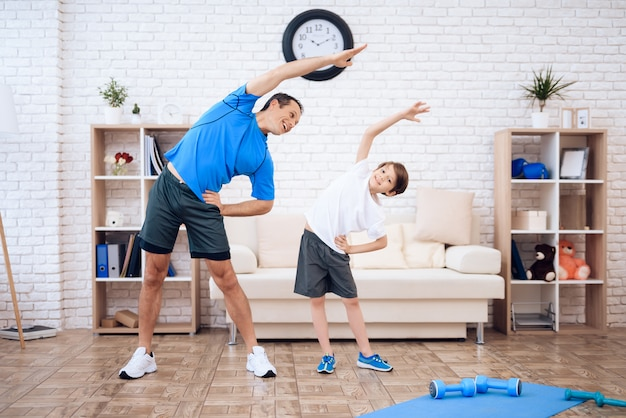 O homem e o menino estão envolvidos em ginástica.