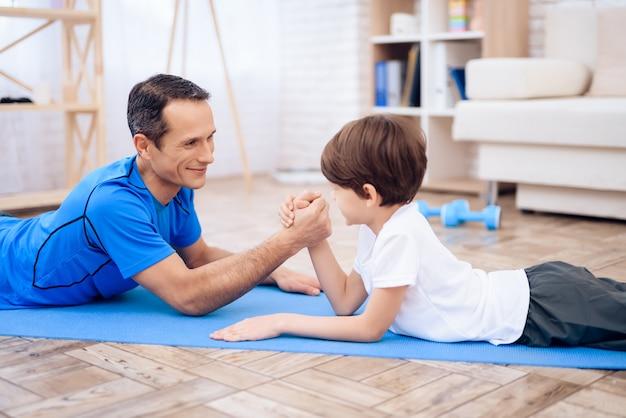 O homem e o menino estão envolvidos em luta de braço.