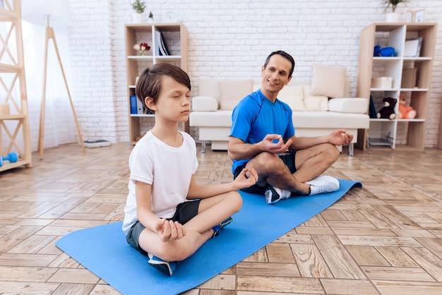 O homem e o menino estão envolvidos em yoga.