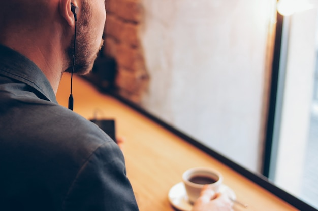 O homem em fones de ouvido usando telefone celular, sentado com café no café