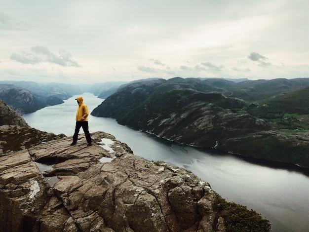 O homem em jaquetas amarelas está perto de uma bela paisagem