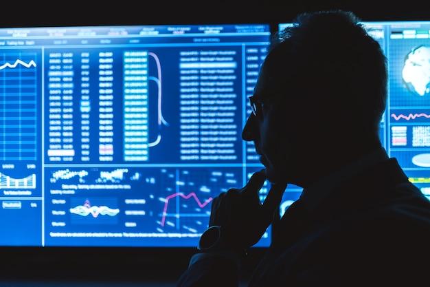 O homem em pé perto da tela azul com gráficos na sala escura