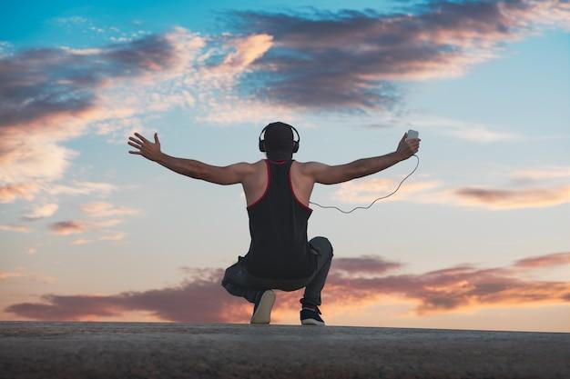 O homem em seus ouvidos levantou as mãos. céu do amanhecer em segundo plano. vista de trás