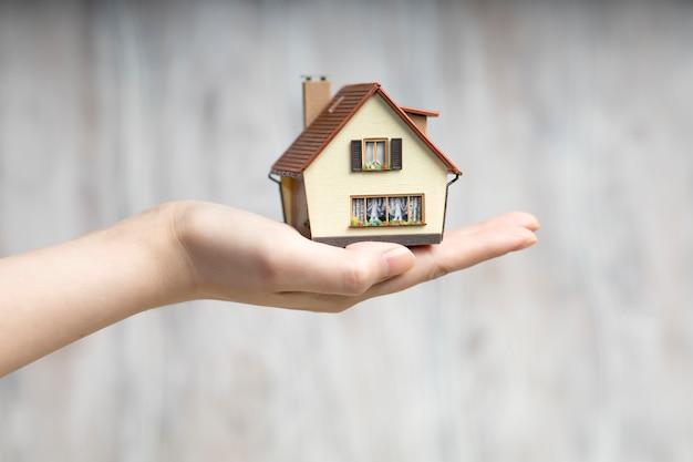 O homem em suas mãos segura uma cópia pequena da casa.