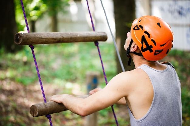 O homem em um capacete de laranja subiu uma escada de corda
