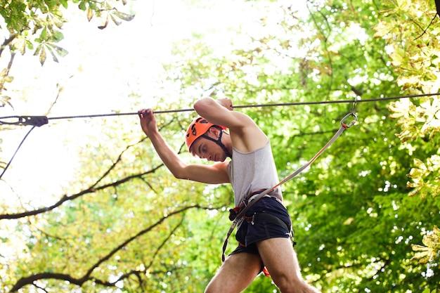 O homem em um capacete laranja está pronto para escalar a corda