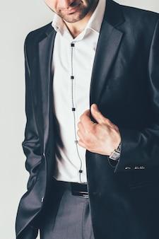 O homem em um terno clássico luxuoso levanta em uma sessão de foto. ele segura uma jaqueta preta com os dedos