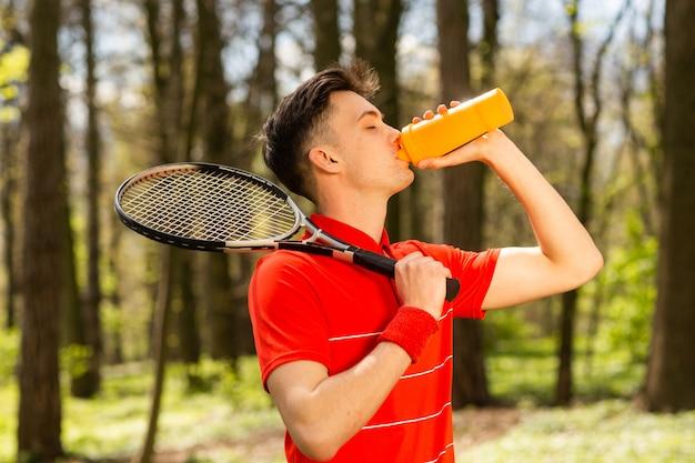 O homem em uma camiseta vermelha posar com uma raquete de tênis e beber água de um termopar.