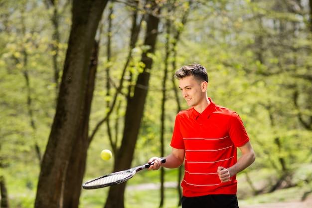 O homem em uma pose vermelha do t-shirt com uma raquete de tênis e uma bola no fundo do parque verde.