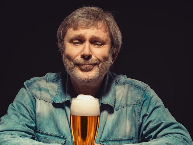 O homem encantado em camisa jeans com copo de cerveja