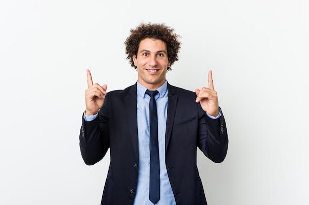 O homem encaracolado do negócio novo contra a parede branca indica com os dois dedos dianteiros que mostram acima um espaço em branco.