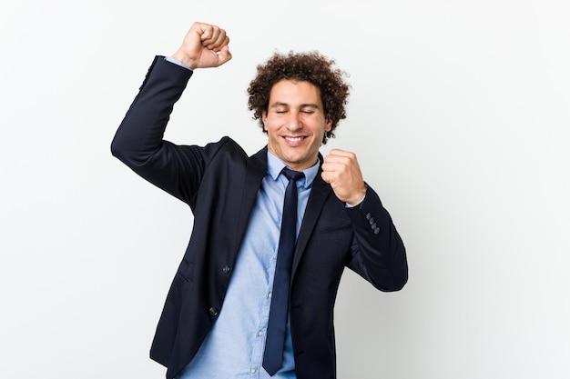 O homem encaracolado do negócio novo contra a parede branca que comemora um dia especial, salta e levanta os braços com energia.