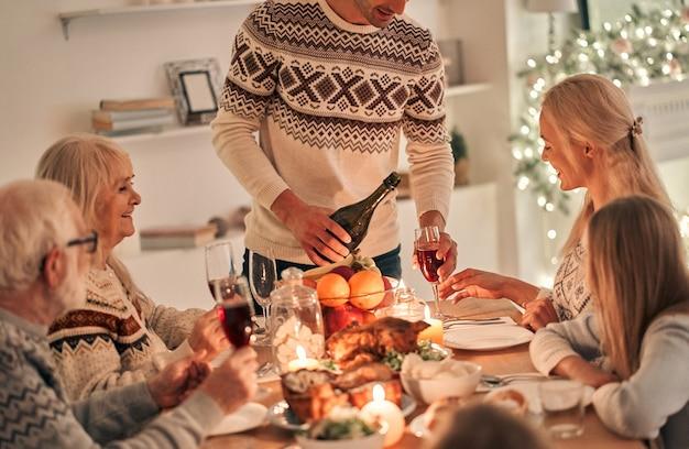 O homem enche as taças de vinho acima da mesa festiva