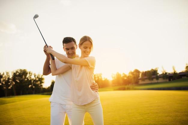 O homem ensina a esposa tomar o passatempo da família do tiro de golfe.