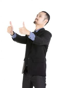 O homem entusiasmado asiático vestiu-se no vestuário formal que dá o thumbs-up.