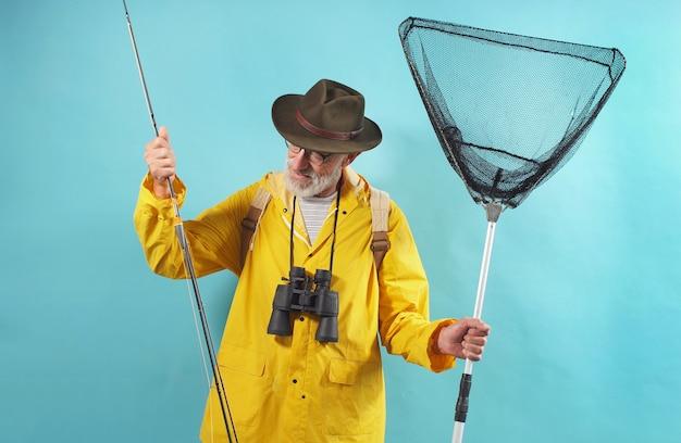 O homem envelhecido em uma capa de chuva amarela e em vidros está indo pescar. um homem com uma vara de pescar e uma rede, parede isolada