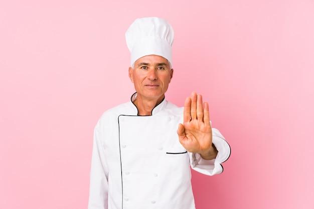 O homem envelhecido médio do cozinheiro isolou a posição com a mão estendida que mostra o sinal de parada, impedindo-o.