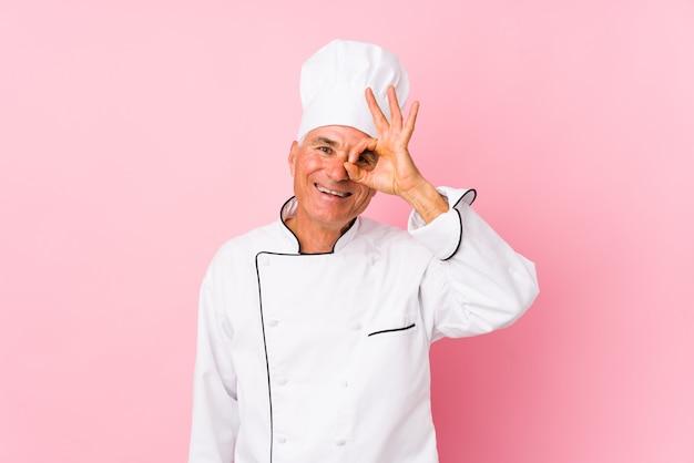O homem envelhecido médio do cozinheiro isolou entusiasmado mantendo o gesto aprovado no olho.