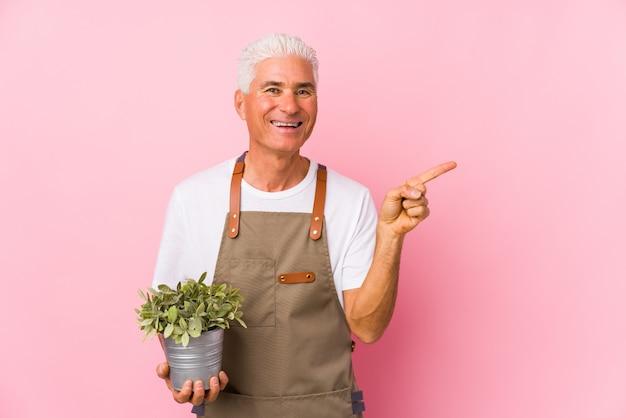 O homem envelhecido médio do jardineiro isolou o sorriso e apontar de lado, mostrando algo no espaço em branco.