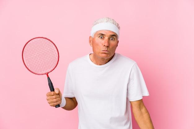 O homem envelhecido médio que joga badminton encolhe os ombros dos ombros e abre os olhos confusos.