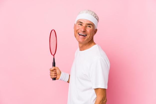 O homem envelhecido médio que joga o badminton isolado olha de lado o sorriso, alegre e agradável.