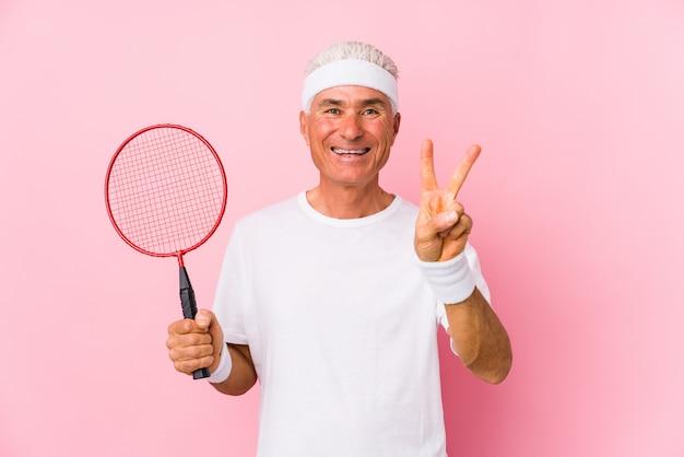 O homem envelhecido médio que joga o badminton isolou mostrar o número dois com dedos.